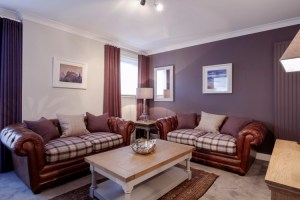 Living Room of the Parkgate Residence showing leather sofas with tartan cushions