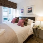 The McDonald Residence double bedroom in mauve tartan, with framed photography of Edinburgh