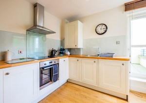 bright and airy kitchen with cream units and wooden worksurface in holiday apartment Edinburgh Old Town