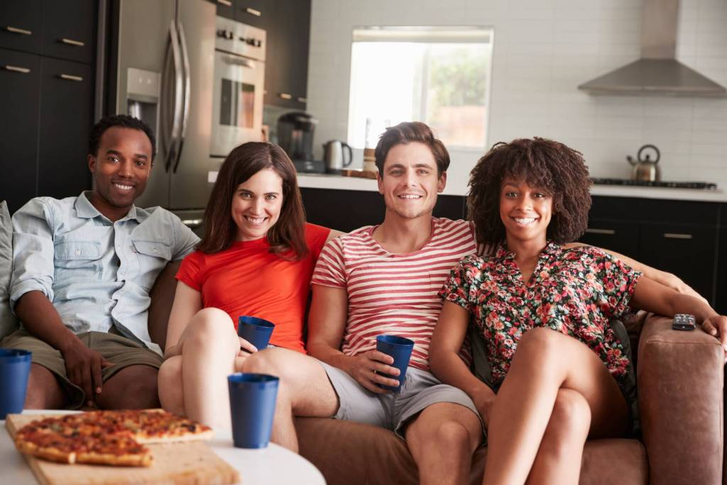 Canva Four Young Adult Friends Relaxing On Couch Together At Home Scaled