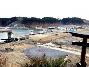 南三陸町、歌津、三島神社へ登る階段から。<br />左は、湾を横断する歌津バイパスの落橋。右側の空き地には集落があった。