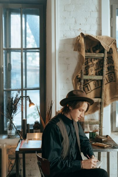 young man writing in vintage clothes for blog First Person and Third Person Points of View