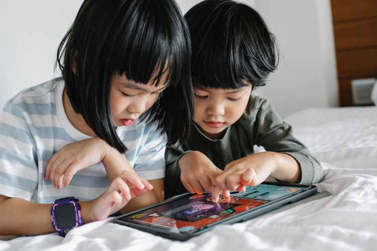 asian kids playing with tablet