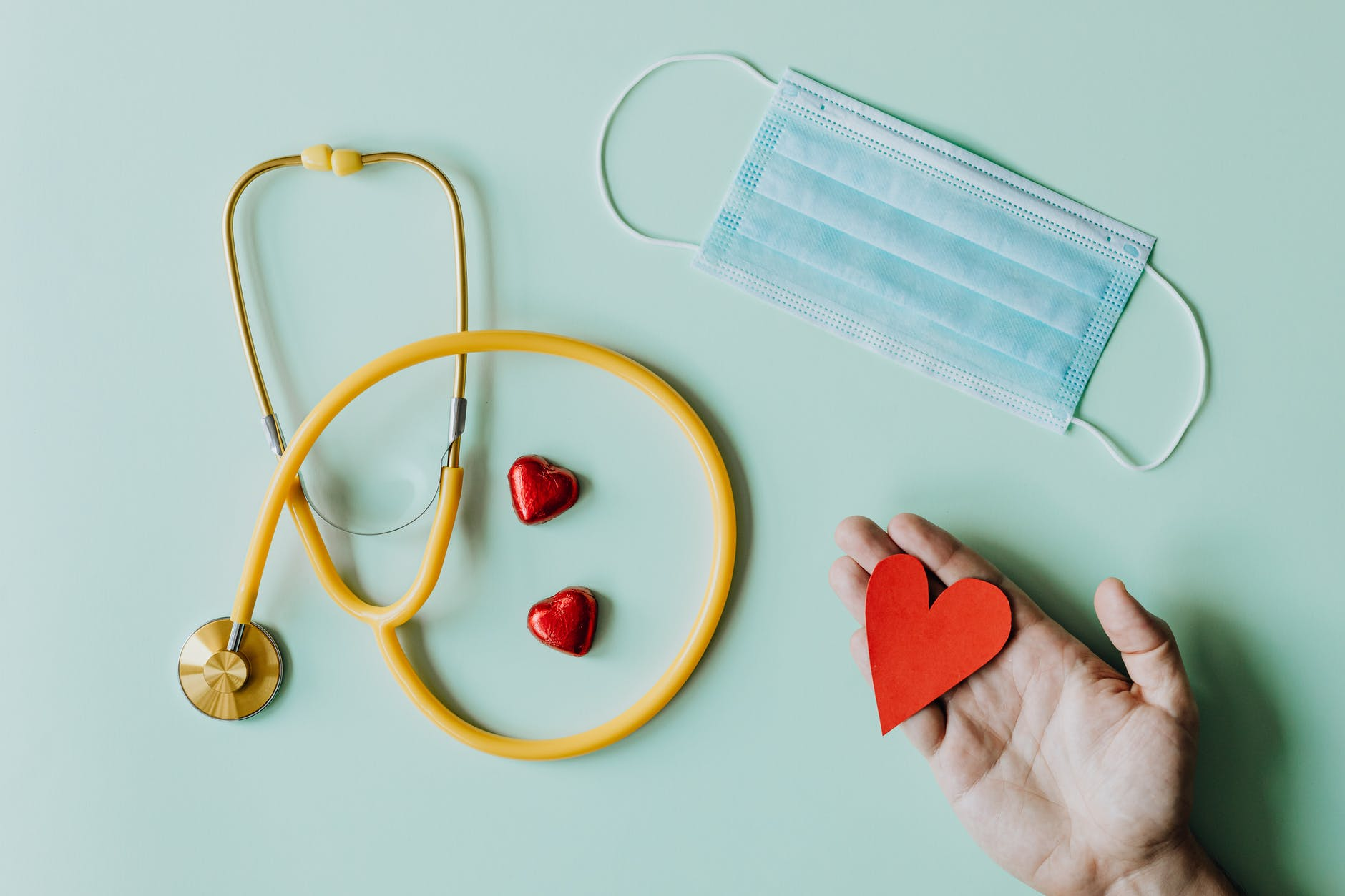medical stethoscope and mask composed with red foiled chocolate hearts