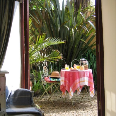 breakfast laid beyond open bedroom french doors
