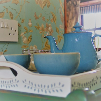 Vintage denby tea pot against vintage wallpaper design