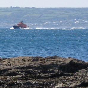 The Penlee lifeboat in Mounts Bay with Mousehole beyond