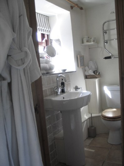 Bathrobes and a neat wash basin in a B&B en suite bathroom
