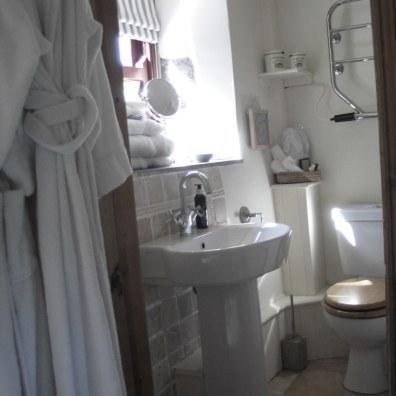 Bathrobes and a neat wash basin in a B&B en suite bathroom