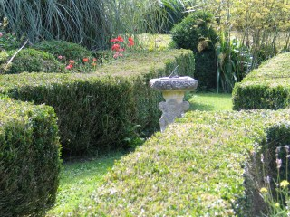 A sundial with the four ages of women forms a centre piece to one small formal garden
