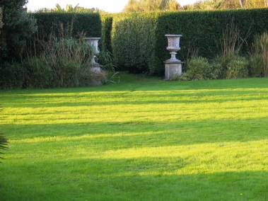 lush green lawn to Italian gardne entrance framed by urns