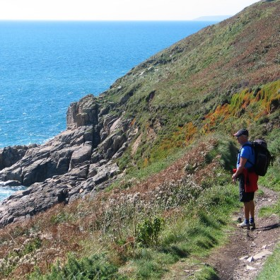 Charles walkingdown teh path towrads Rinsey with the spectacular backdrop of the sea