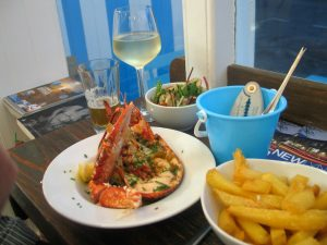 Half a lobster with salad and chips with a chic bucket holding tooles for opening the lobster claws at Mackerel Sky seafood bar