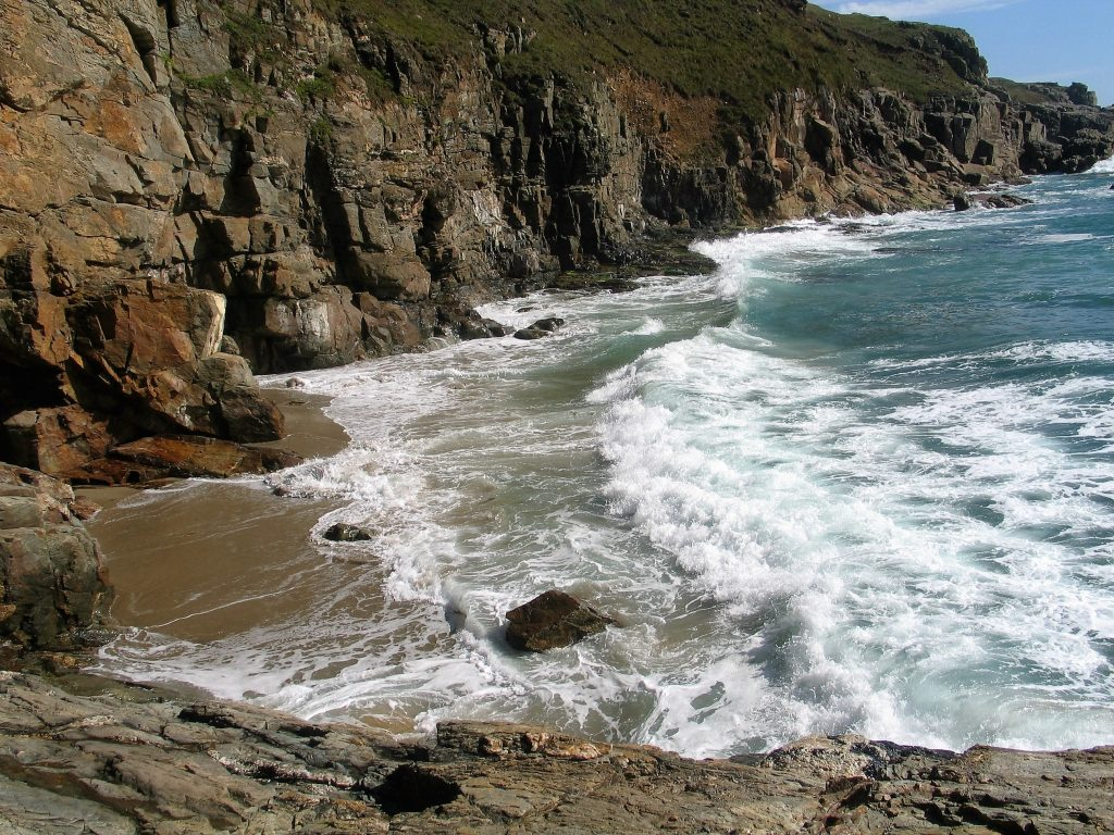 Explore the secret beach at Rinsey  with soft sand and imposing cliffs flanking the cove