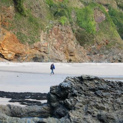 Lone figure walking on an empty beach