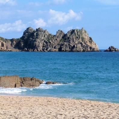 Blueseas and sky wit granite headland beyond a beach