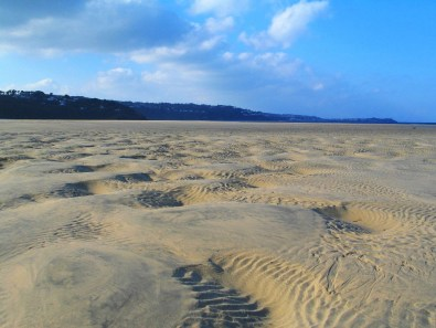 Sands exposed by the retreating tide carved into reverlets by the sea