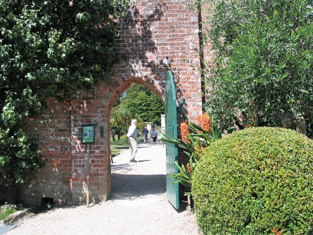 Old arched doorway into an immaculate kitchen garden