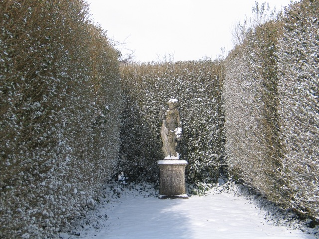 winter snow makes a christmas scene statue in a formal garden