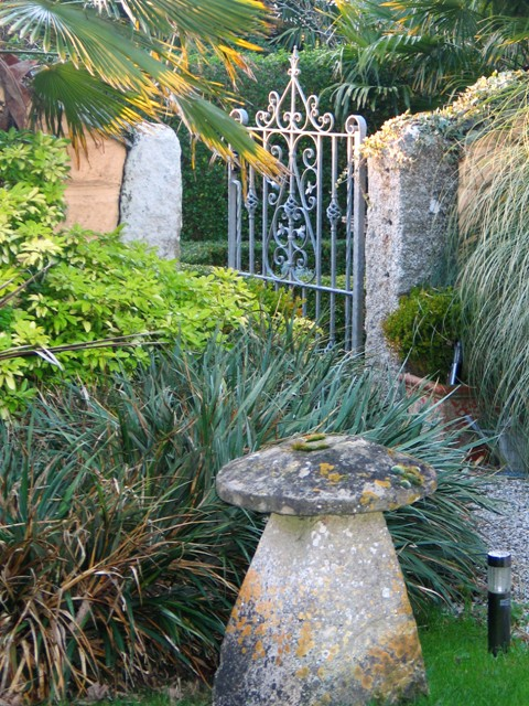 Stone mushroom and garden gate flanked by granite posts