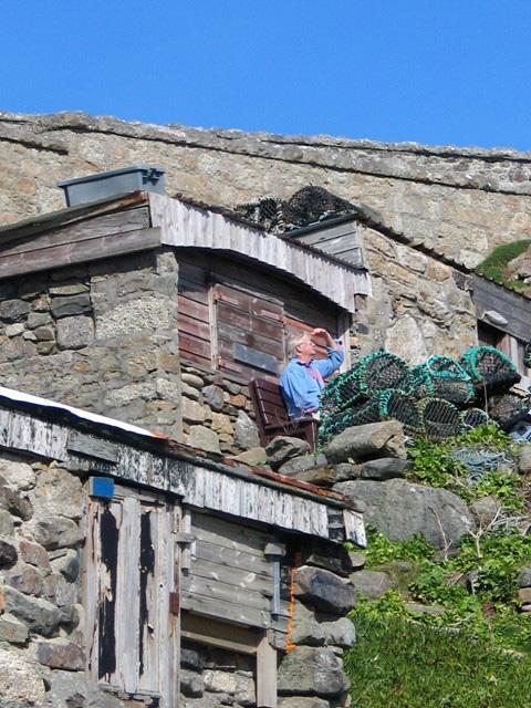 Man bird watching beside fishing hut