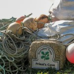 Tangle of fishing equipment stacked beside National Trust sign - Priest's Cove