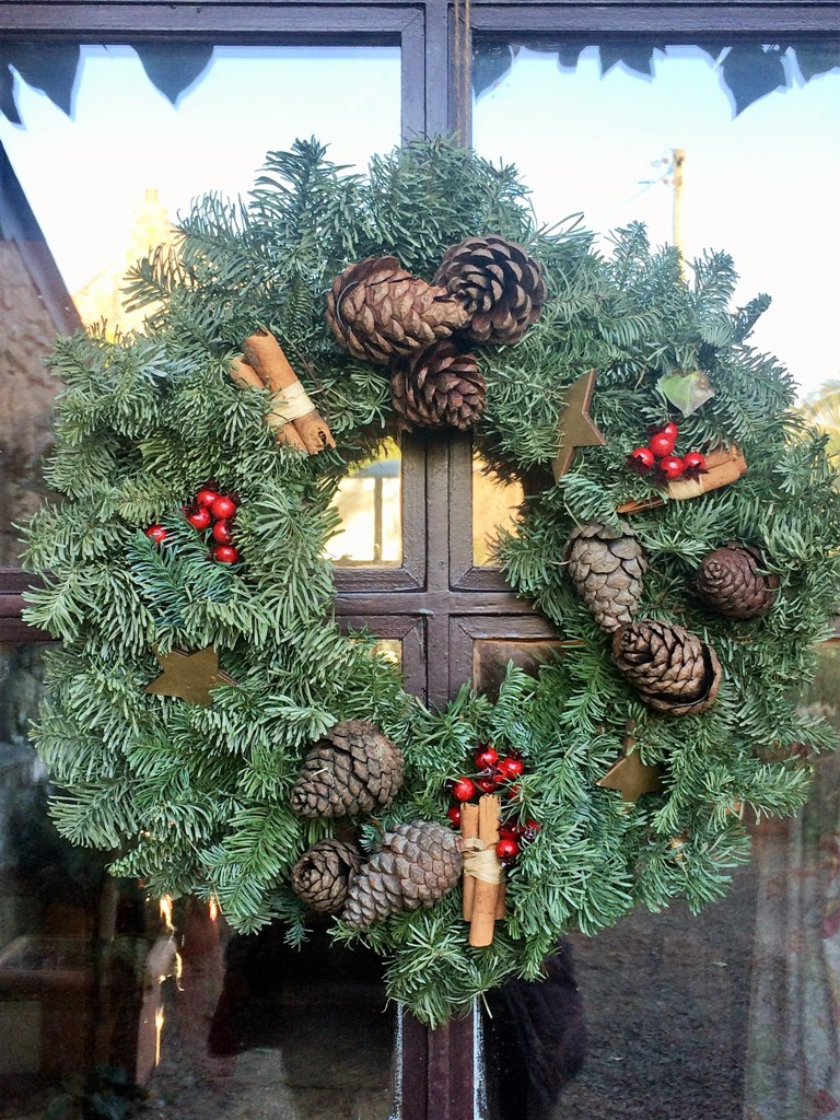 A traditional Christmas door wreath lends a gogeous pine scent