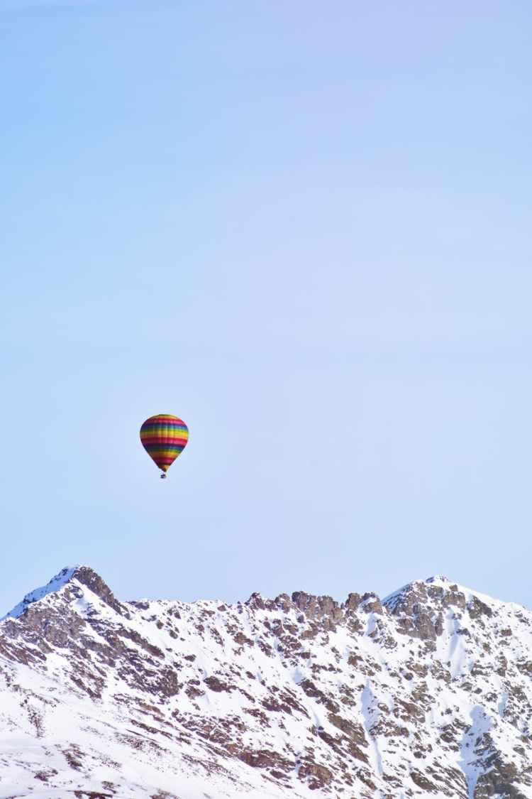 flying hot air balloon above snow covered mountain