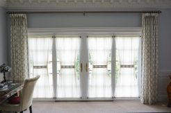 Goblet pleated drapes with accent ties and sheer stationary shades