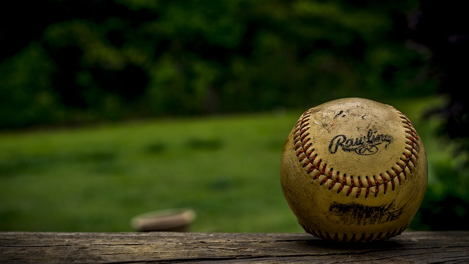 A close-up of a baseball on a bench.