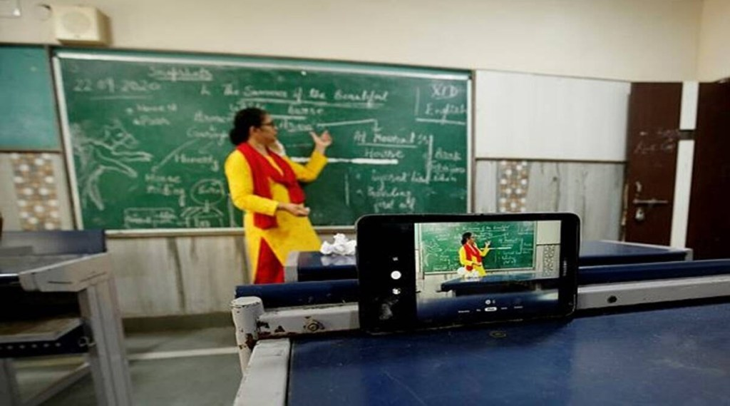 teacher stands in front of board while streaming live from a mobile phone