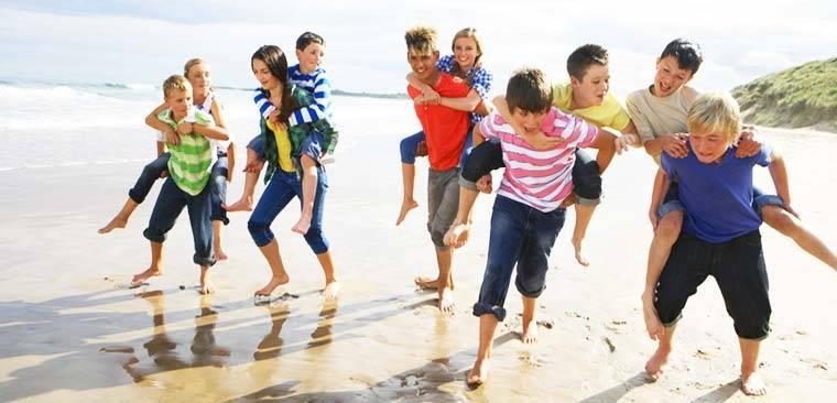 Groupe d'amis qui portent enfants sur le dos à la plage