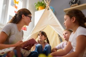 homeschooling while pregnant mom reading to children on the floor near a teepee