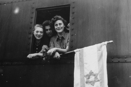 Children looking out a train car window holding a flag