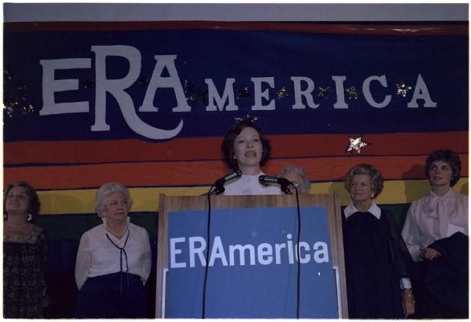 Rosalynn Carter speaking in front of an ERAmerica sign