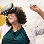 A woman smiling while wearing virtual reality headset