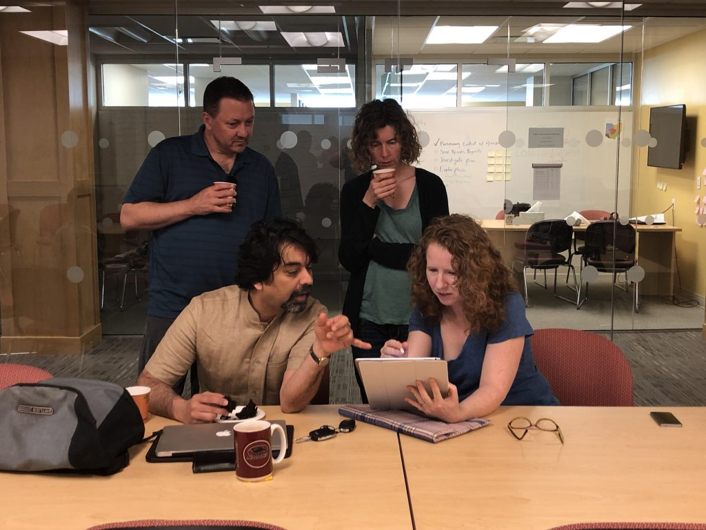 Two men and two women gathered around an iPad