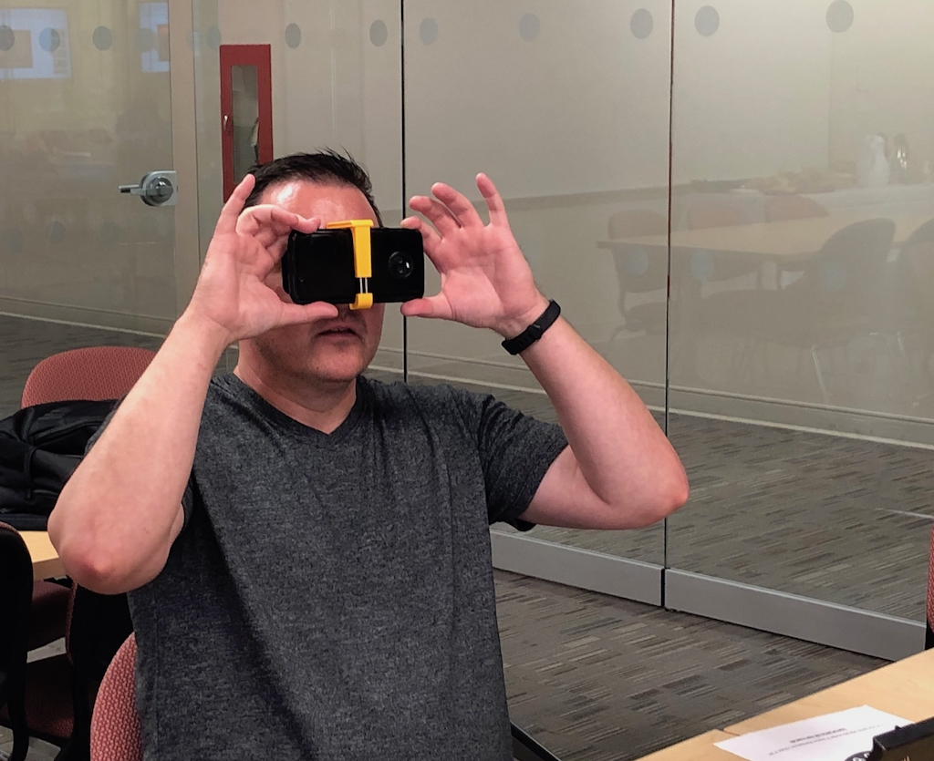 man looking at smartphone attached to viewer