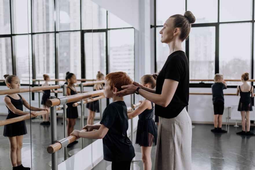 a woman teaching a boy in a dance class