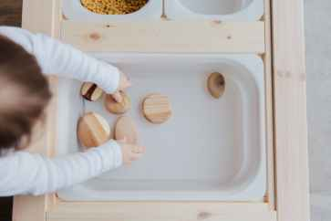 Image showing child collecting easily moveable objects to play a game of NIM