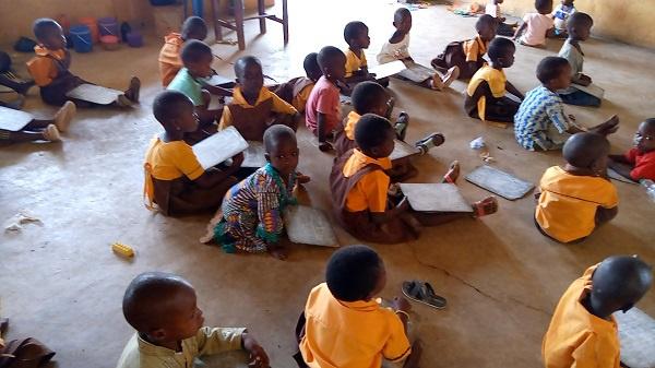 Kindergarten pupils of the school sitting on the floor during class