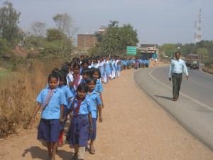 स्कूल की रैली में जाते बच्चे और शिक्षक