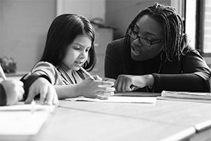 A teacher helps her young student with work.