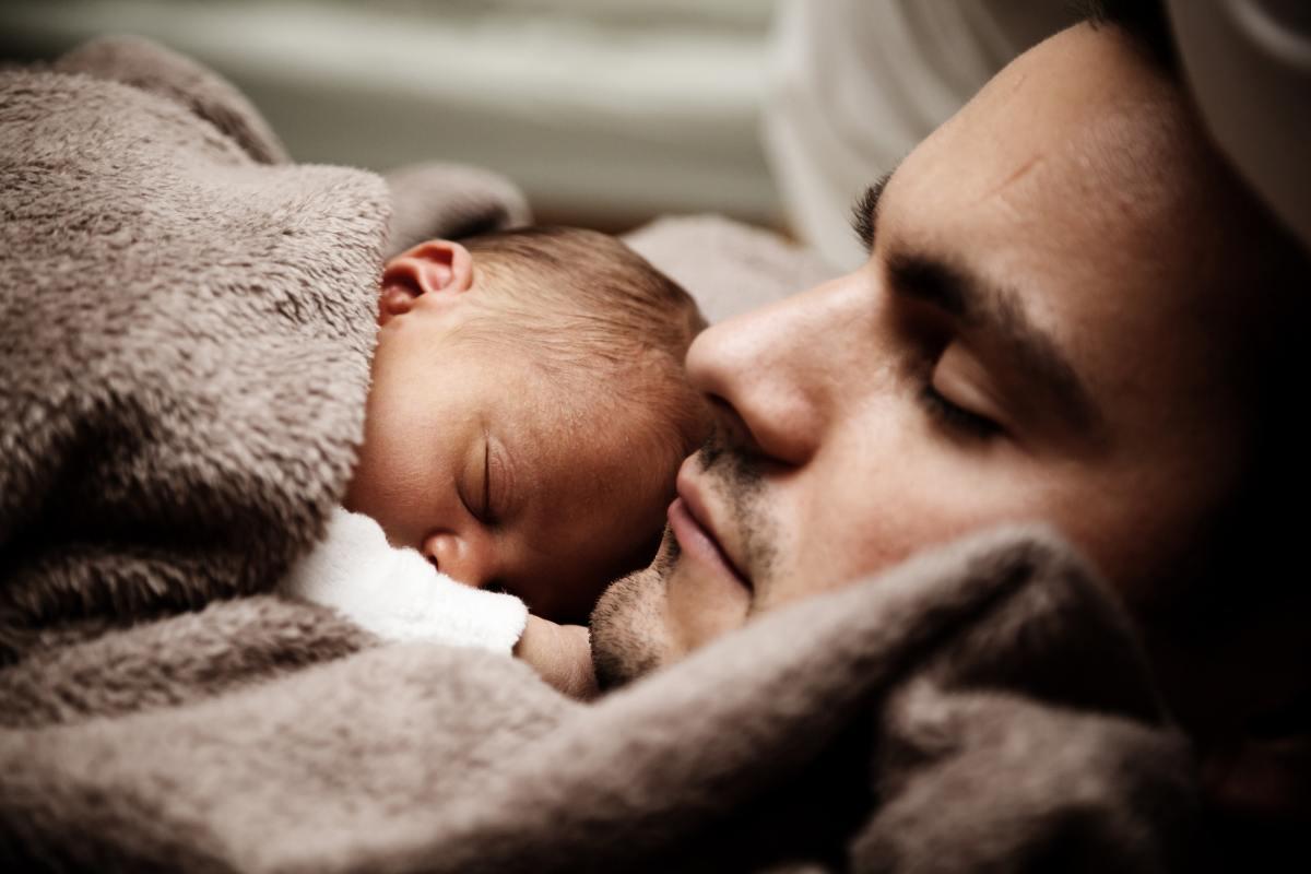 Un nouveau papa dort avec son jeune bébé.