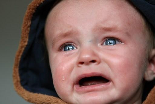 Bébé avec une capuche pleure