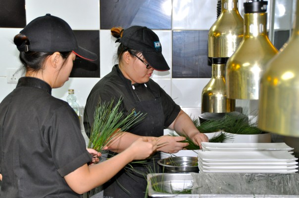 Students preparing the pine needles for the dish