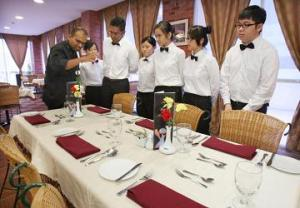Students being briefed by KDU Penang School of Hospitality, Tourism and Culinary Arts programme leader Prakash R. Jakathesan on the art of table settings.