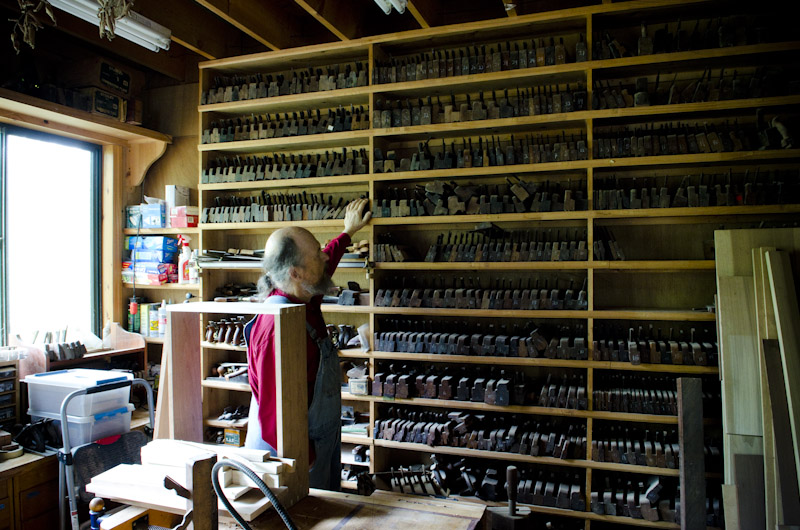 Bill Anderson looking at his wall of molding planes in his woodworking workshop