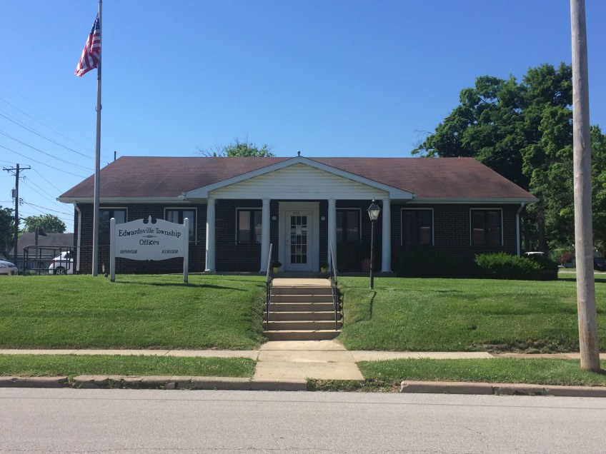 Daytime photo of the front of the Edwardsville Township brick building with flag, grass and sign.