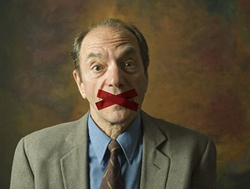 portrait of surprised man with mouth taped shut
